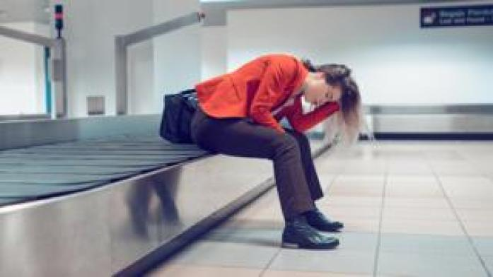 Woman with head in hands sitting on baggage carousel