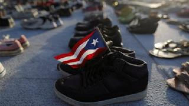 A Puerto Rican flag is seen on a pair of shoes among hundreds displayed at the Capitol