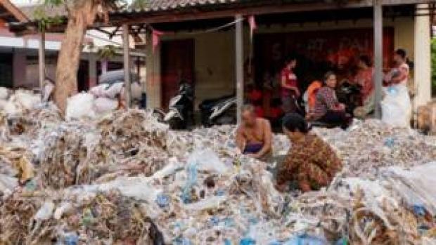 Villagers sort through plastic