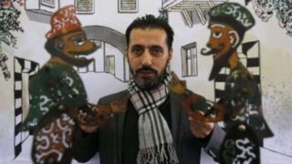 Syrian last shadow puppeteer Shadi al-Hallaq holds his puppets Karakoz (L) and Eiwaz (R) before a presentation in Damascus on 3 December 2018.