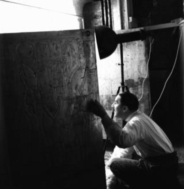 Howard Carter peering into the burial chamber from an opening in a wall engraved with hieroglyphs
