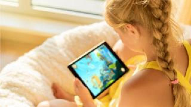 Girl playing a game on an iPad