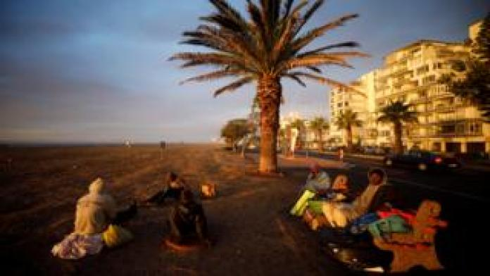 A group of homeless men take in the last of the days light before seeking a place to sleep in South Africa