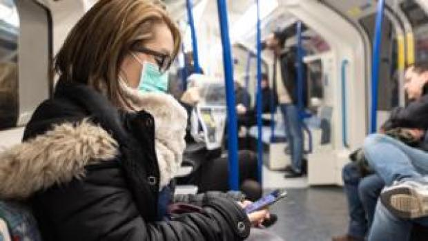 Woman wearing a mask on the London Underground