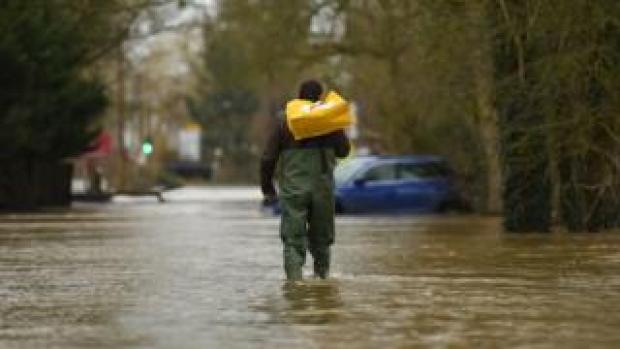 A man wades through floods in Upton upon Severn