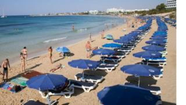 Stock photo of tourists sunbathing on a beach in the resort of Ayia Napa