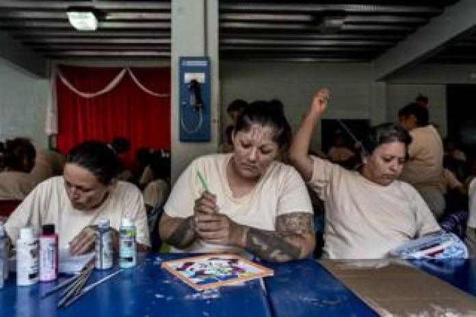 A La 18 gang member paints, center, while another inmate embroider, right, as part of the Yo Cambio program at Ilopango Women's Prison, El Salvador, November 6 2018.