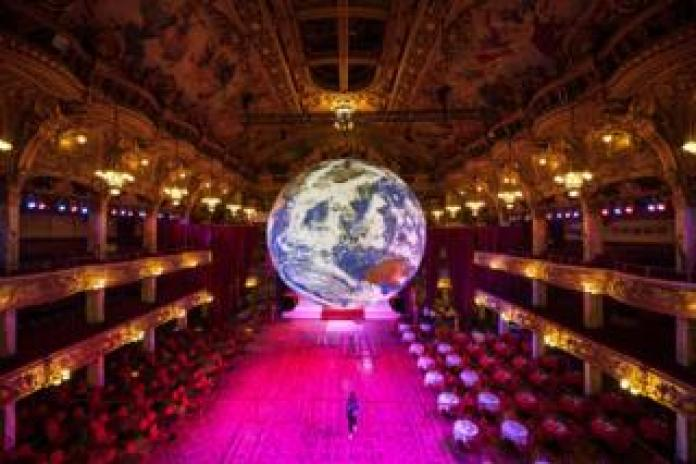 Members of the public admire an illuminated art installation looking like the earth