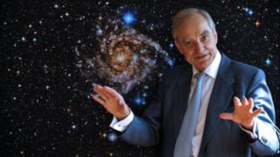 This file photo taken on May 19, 2009 shows French astrophysician Andre Brahic posing in front of a picture of the IC 342 galaxy