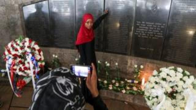 A Kenyan woman (C), who lost her relative, poses for a photo being taken by her friend as she stands in front of the plaque bearing the names of those killed during the 1998 bombing of US Embassy, at the August 7th memorial park in Nairobi, Kenya, 07 August 2018.