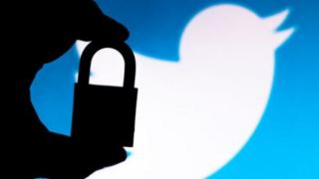 The silhouette of a padlock in front of the Twitter logo