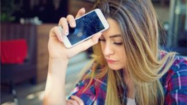 young woman with cracked mobile phone