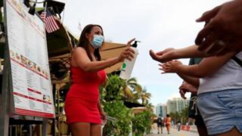 Hostess provides hand sanitiser at restaurant in Miami, 3 Jul 20