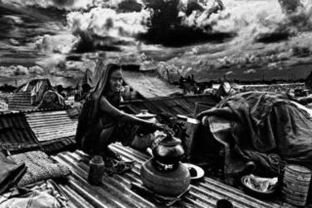 Woman cooking on rooftop, Jinjira, Dhaka, Bangladesh. 1988.