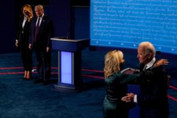 Joe Biden is embraced by his wife Jill as Donald Trump stands next to First Lady Melania Trump at the end of their first 2020 presidential campaign debate