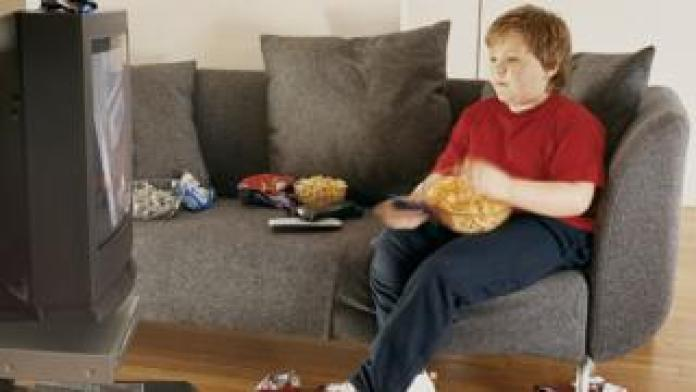 Child watching TV, eating junk food