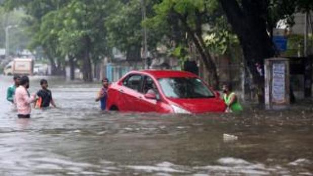 People help a woman to move her car through a water-logged road during rains in Mumbai, August 29, 2017