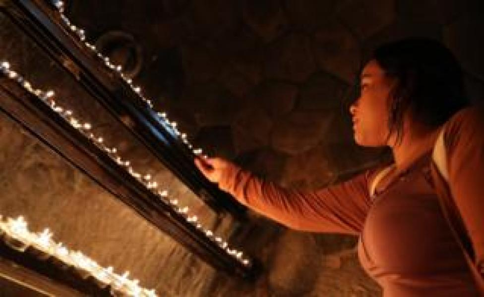 A worshiper lights a candle at St. Joseph