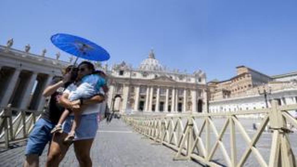 A couple with a child try to protect themselves against the sun with a parasol as they walk near the Vatican