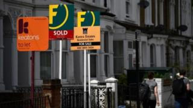 Sale signs outside properties