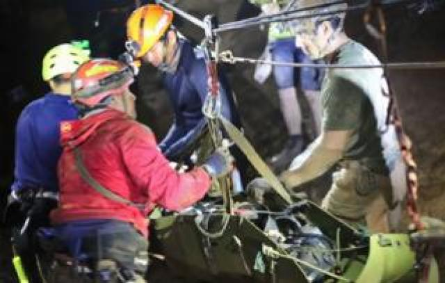 Boy being moved by rescuers inside the cave