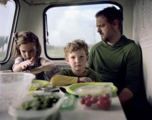 A family sit in their caravan.