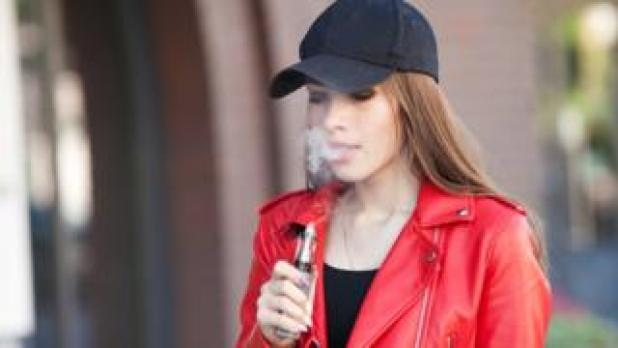 Young woman vaping on the street
