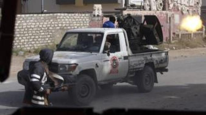 A Libyan fighter loyal to the Government of National Accord (GNA) fires a truck-mounted gun during clashes