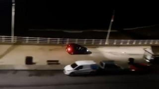 A black car driving along the seafront