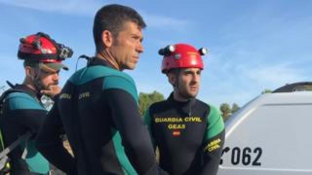Three men in wetsuits and hard hats, emblazoned with the logo of the Spanish civil guard, stand by their vehicle, gazing into the middle distance beyond the frame