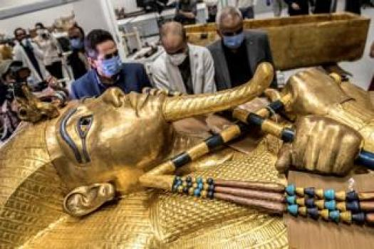 The golden sarcophagus of the ancient Egyptian Pharaoh Tutankhamun lies in the restoration lab as workers look on