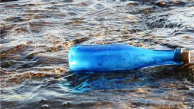 Blue bottle floating in the sea
