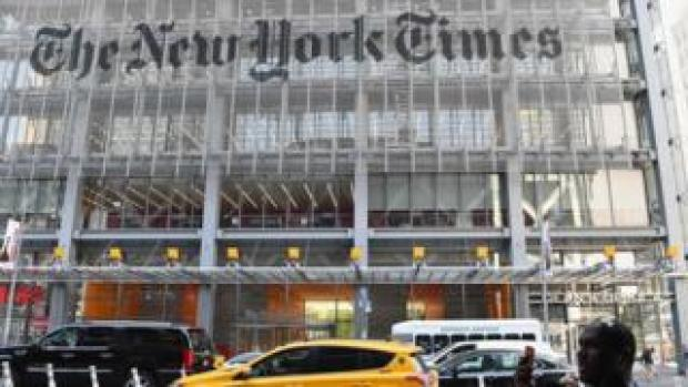 In this file photo a man holds his smartphone in front of the New York Times building on September 6, 2018 in New York