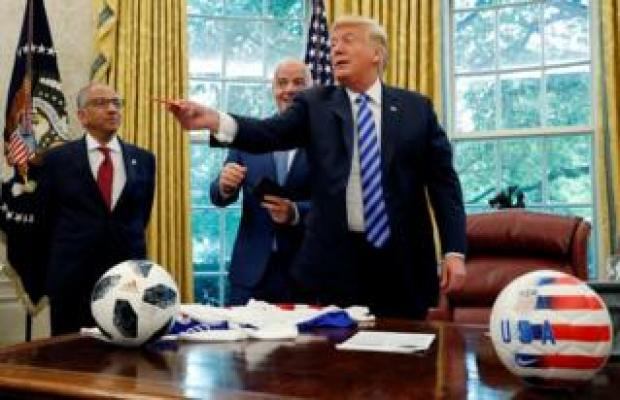 US President Donald Trump pretends to throw a red card at the news media