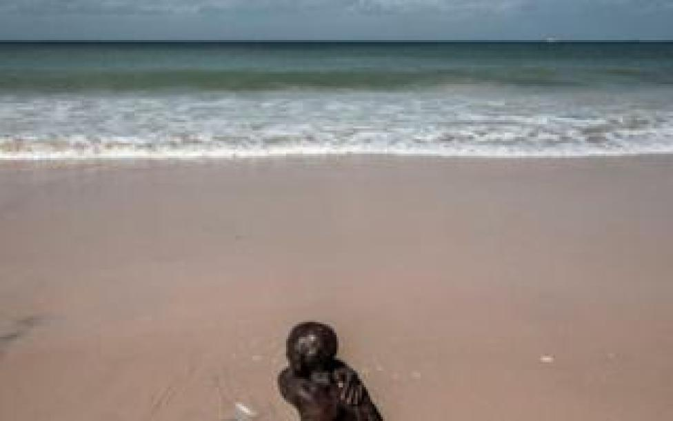 A Senegalese man cleans himself along the coastline in Bargny on August 15, 2020.