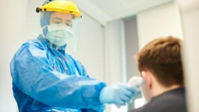WHO guidelines, which currently recommend health staff wear a full gown and visor.
