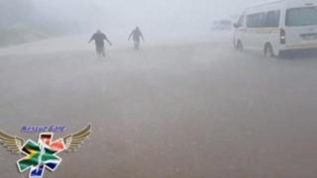 People wade through flood water in strong winds and rain next to submerged vehicles on a road during stormy weather in Durban, South Africa , 10 October 2017