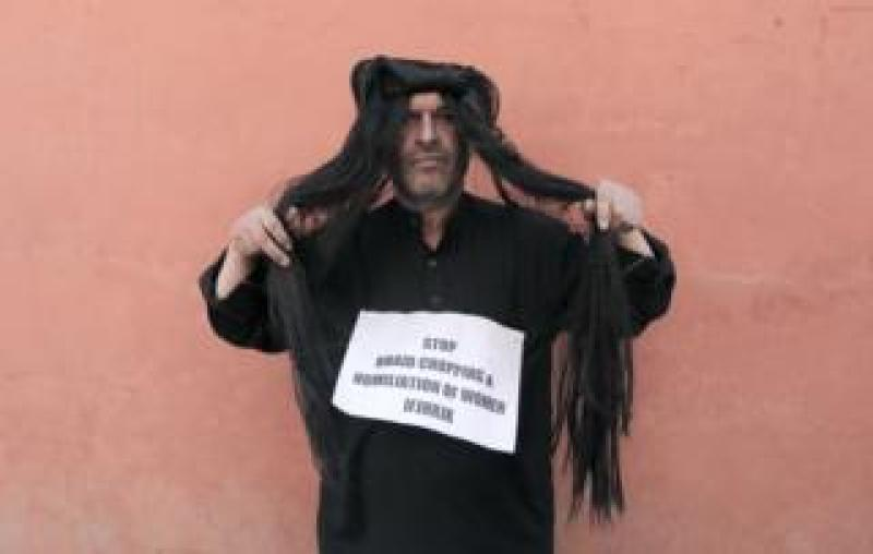 """Ahsan Antoo wears a wig of long hair while holding a sign that says """"stop braid chopping and humiliation of women"""" in Kashmir"""