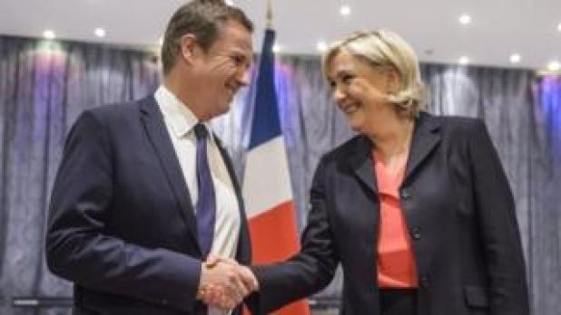 Nicolas Dupont-Aignan (L) and Marine Le Pen (R) shake hands after delivering a joint news conference in Paris, France (29 April 2017)