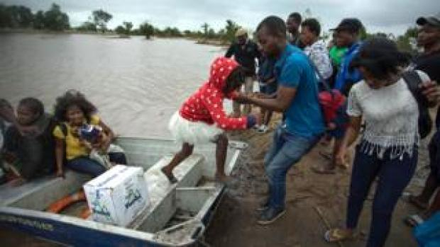 Families affected by Cyclone Idai get off a boat in Beira, Mozambique