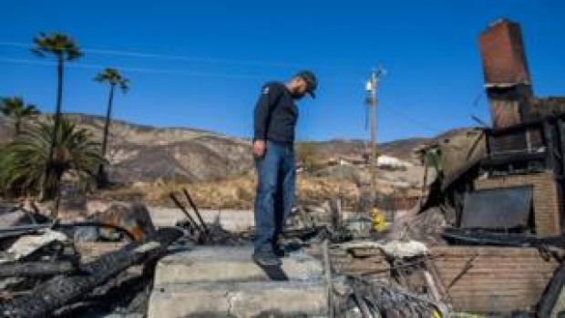 Matthew Valdivia looks for personal objects among the ashes of his home at Viento Way bear San Bernardino, California, on 31 October