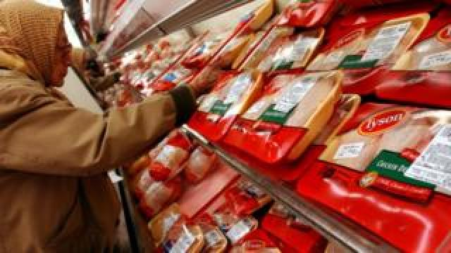 A supermarket shopper examines the chicken products produced by Tyson