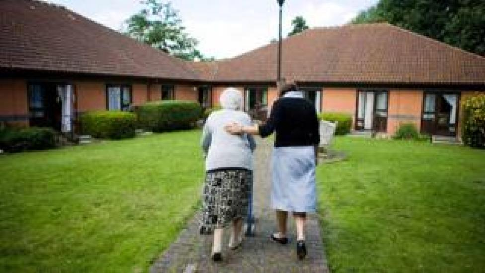 old lady and helper in residential care complex