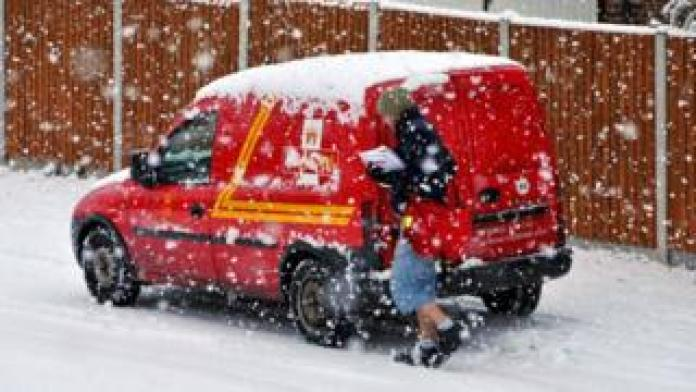 A Royal Mail postal worker in the snow