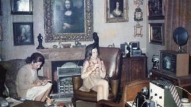 Two women sit beneath a Mona Lisa painting hanging above the fireplace of a 1960s London flat