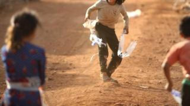 Children, with identities hidden, in a camp near Idlib