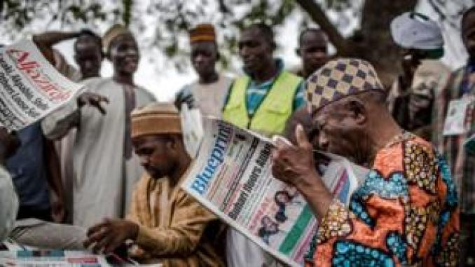 Man reads newspaper announcing election result in Kano, Nigeria