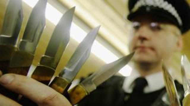 An officer holds knives handed in to police
