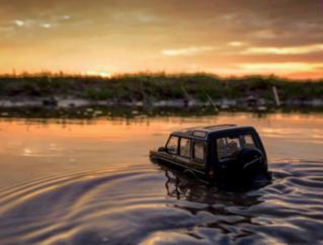 Model Land Rover drives through a river
