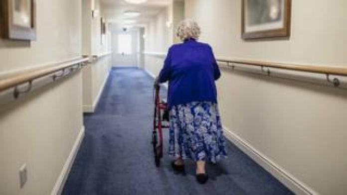 old lady walking down the hall in nursing home